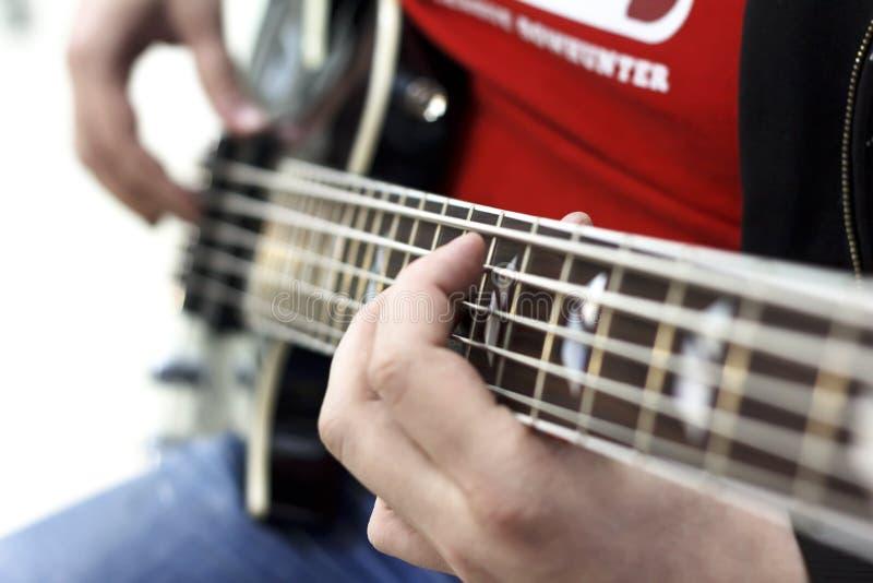 关闭在弹在阶段的音乐家的手指低音吉他 免版税库存照片