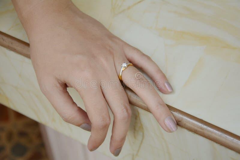 关闭在手指的典雅的钻戒有羽毛和灰色围巾背景的 库存图片