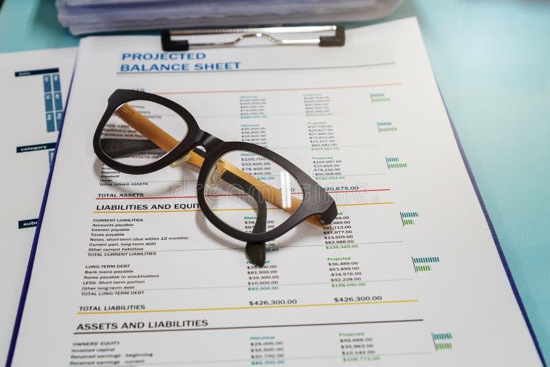 关闭在报告文书工作的眼睛玻璃与图在企业工作场所 免版税库存照片