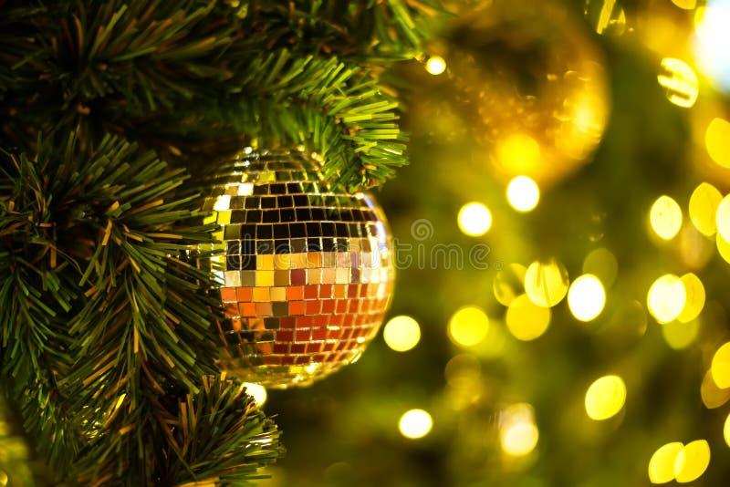 关闭在抽象轻的金黄bokeh背景的圣诞树装饰金球  免版税库存图片