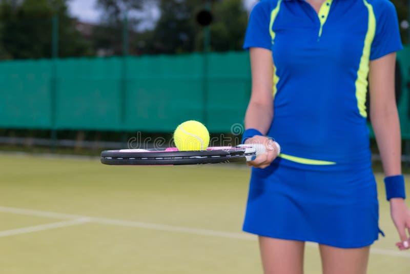 关闭在拿着在她的球拍的一个女性球员网球 免版税库存照片