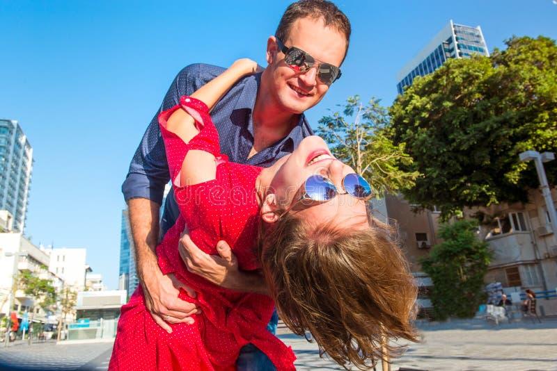 关闭在明亮的获得衣裳和的太阳镜的情感年轻愉快的夫妇乐趣户外 跳舞在街道的微笑的恋人 库存图片