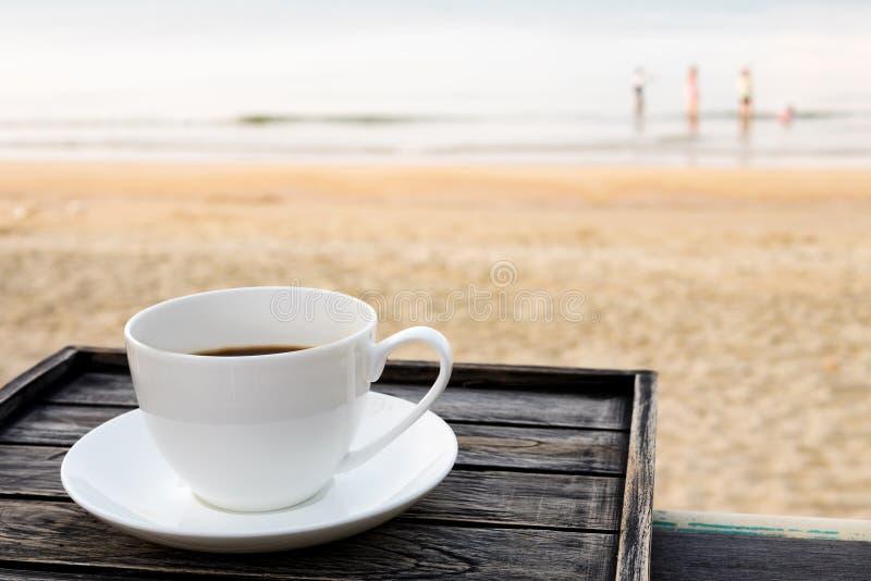 关闭在木桌上的加奶咖啡杯子在日出沙子海滩早晨 免版税库存照片