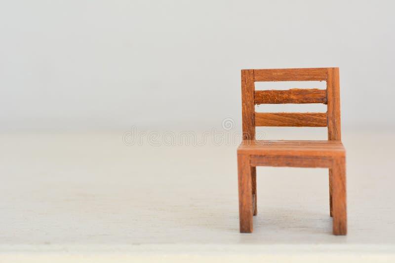 关闭在木桌上的微型玩具椅子 免版税库存图片
