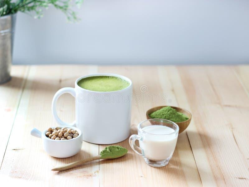 关闭在木桌上的热的绿茶拿铁与白色backgro 库存图片
