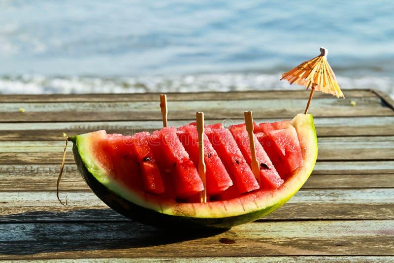 关闭在木桌上的西瓜在海边附近 库存照片