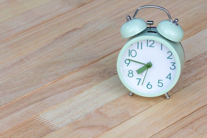 关闭在木桌地板安置的绿色闹钟 库存图片