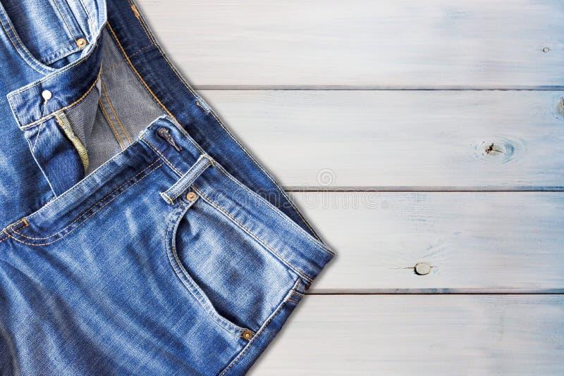 关闭在木背景的牛仔裤裤子 免版税图库摄影