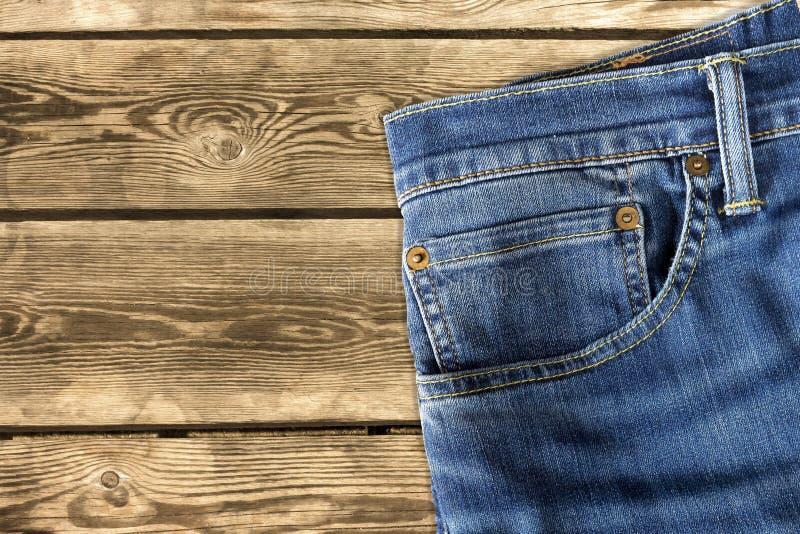 关闭在木背景的牛仔裤裤子 库存照片