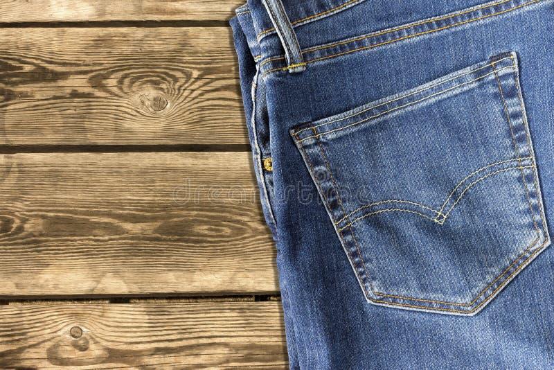 关闭在木背景的牛仔裤裤子 免版税库存图片