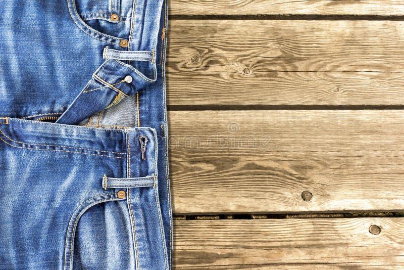 关闭在木背景的牛仔裤裤子 免版税库存照片