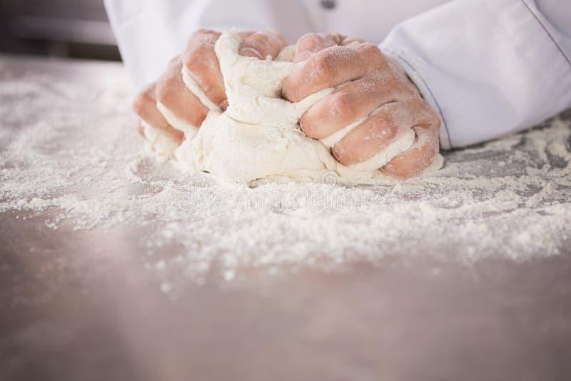 关闭在柜台的面包师揉的面团 免版税库存照片