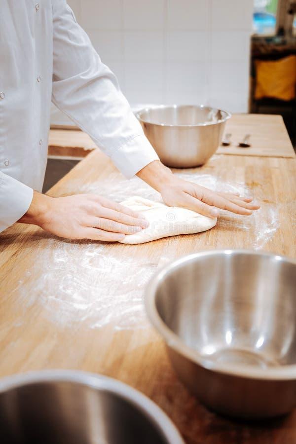 关闭在桌上的面包师揉的面团早晨 库存照片