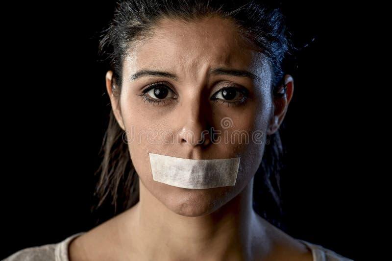 关闭在橡皮膏密封的年轻可爱的妇女和嘴唇画象有嘴的被克制 免版税库存照片