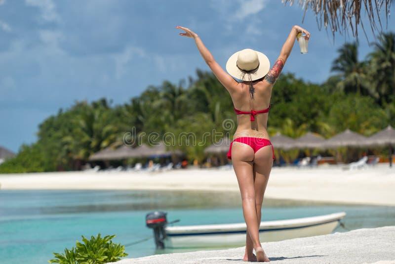 关闭在比基尼泳装的女孩后面反对海洋海滩和鸡尾酒 免版税库存照片