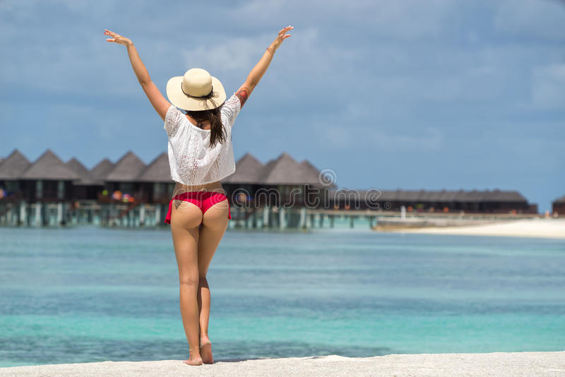关闭在比基尼泳装的女孩后面反对海洋海滩 免版税图库摄影