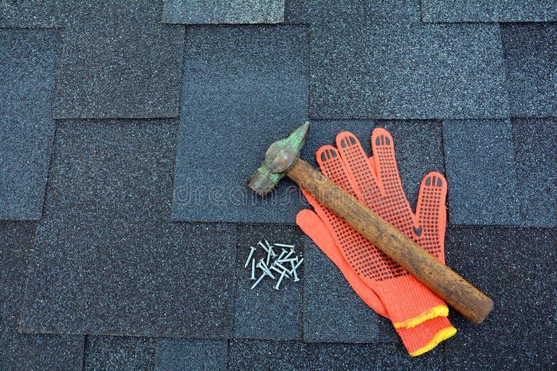 关闭在沥青屋面木瓦背景的看法 屋顶木瓦-屋顶 沥青屋面盖锤子、手套和钉子 库存照片