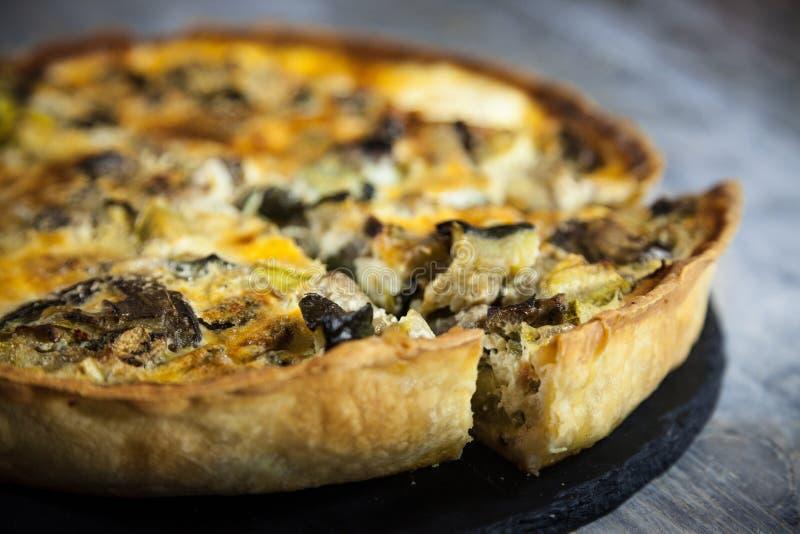 关闭在法国菜乳蛋饼洛林饼的切片裁减在显示的在一张土气木桌上 免版税图库摄影