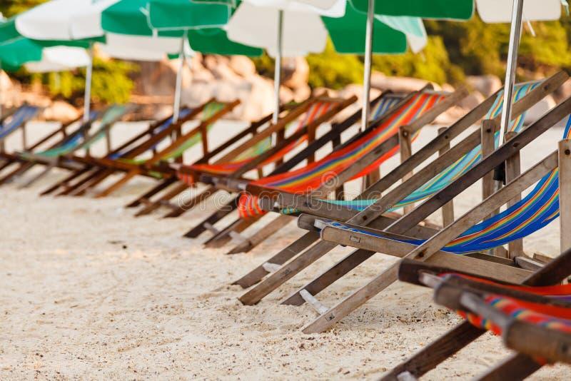 关闭在海滩的五颜六色的海滩睡椅 免版税库存图片