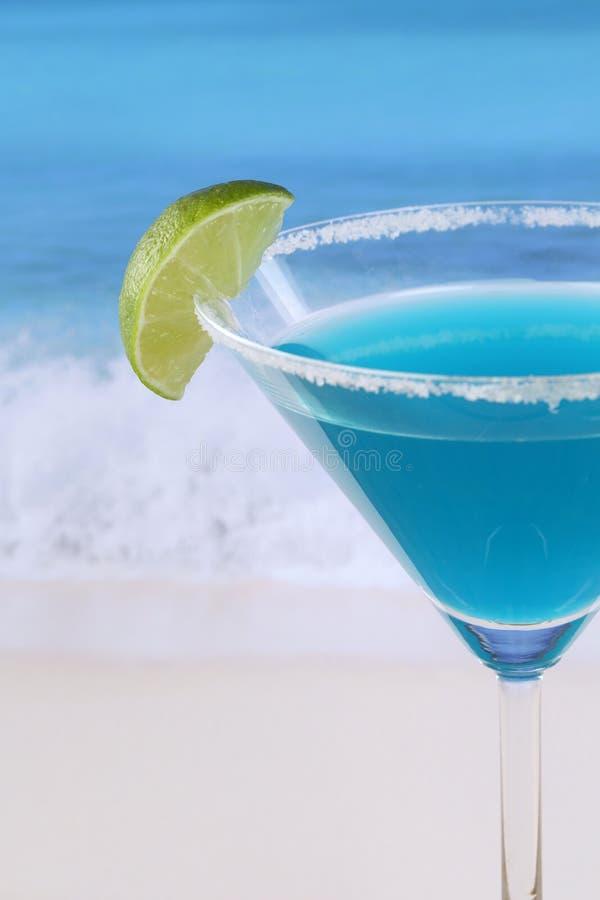 关闭在海滩的蓝色库拉索岛鸡尾酒 免版税库存照片