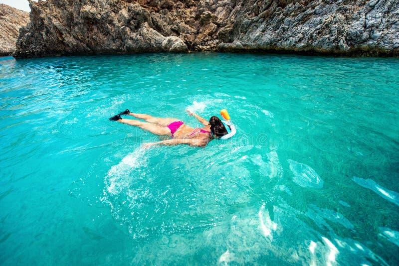 关闭在清楚的海水的妇女游泳,享受潜航在一个热带海岛上 库存图片