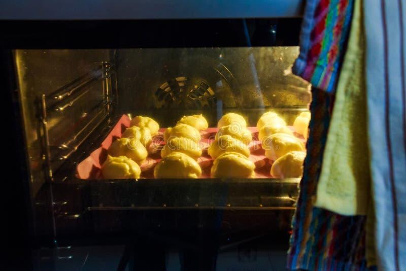 关闭在烤箱的自创profiteroles 免版税库存照片