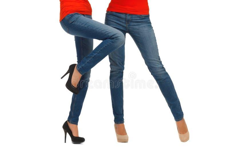 关闭在牛仔裤的两条妇女腿 免版税库存照片