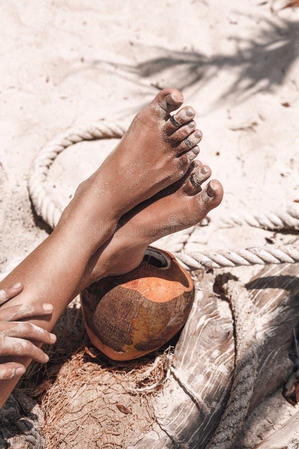 关闭在狂放的海滩的美好的妇女腿用椰子 免版税库存照片