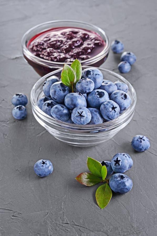 关闭在玻璃碗的看法果酱用新鲜的成熟蓝莓和叶子 库存照片