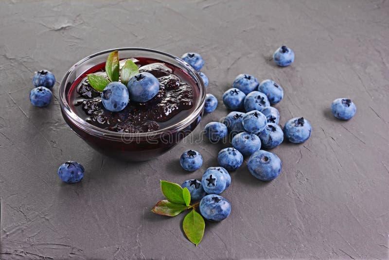 关闭在玻璃碗的看法果酱用新鲜的成熟蓝莓和叶子 免版税图库摄影