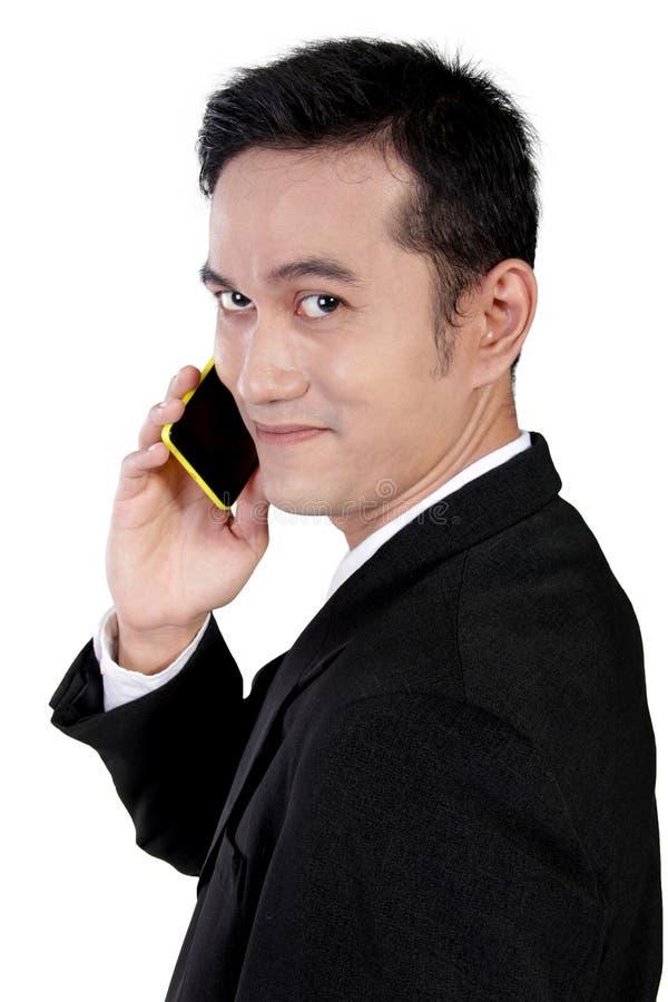 关闭在电话的微笑的商人,隔绝在白色 免版税库存图片