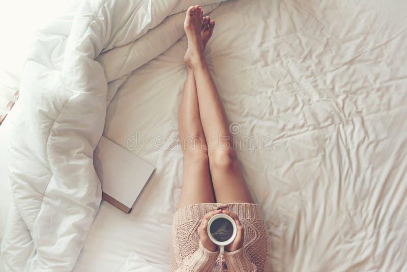 关闭在白色床上的腿妇女 妇女阅读书和饮用的咖啡在早晨放松在冬天季节的心情 库存图片