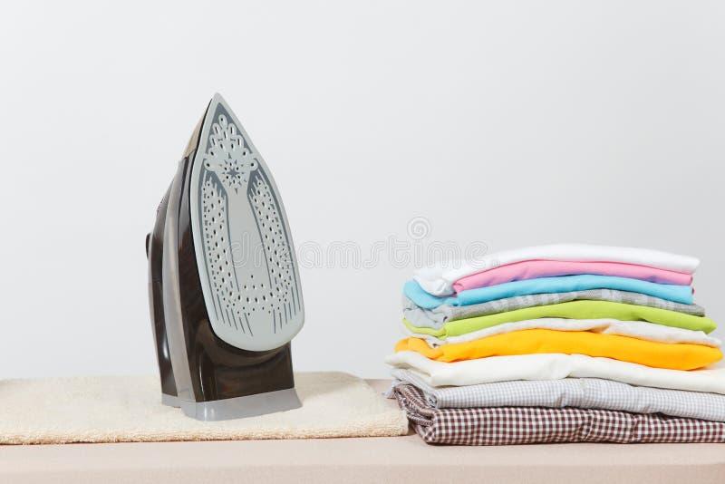 关闭在白色背景的蒸气熨斗五颜六色的衣裳被洗涤的洗衣店 管理 复制空间广告 安置文本 库存照片
