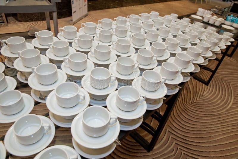 关闭在白色茶碟和木桌的肮脏的咖啡杯和匙子设置在喝以后在葡萄酒样式的早晨 库存图片
