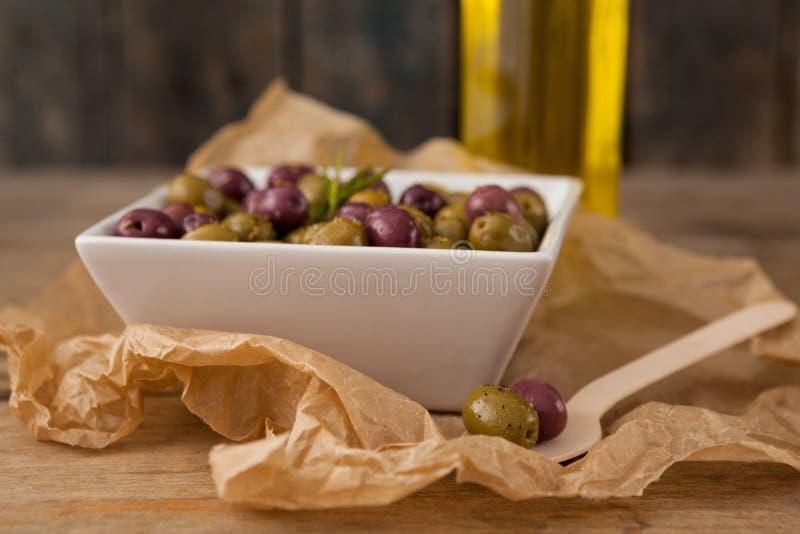 关闭在碗供食的橄榄由木匙子 免版税库存图片