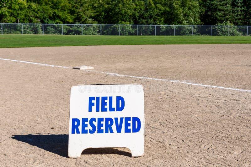 关闭在空的地方棒球场的领域后备的标志,三垒和基础线,与森林的好日子在背景中 免版税库存照片