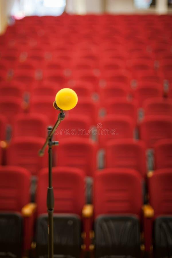 关闭在空的椅子大厅前面的话筒 在会议前,音乐会,研讨会 库存照片