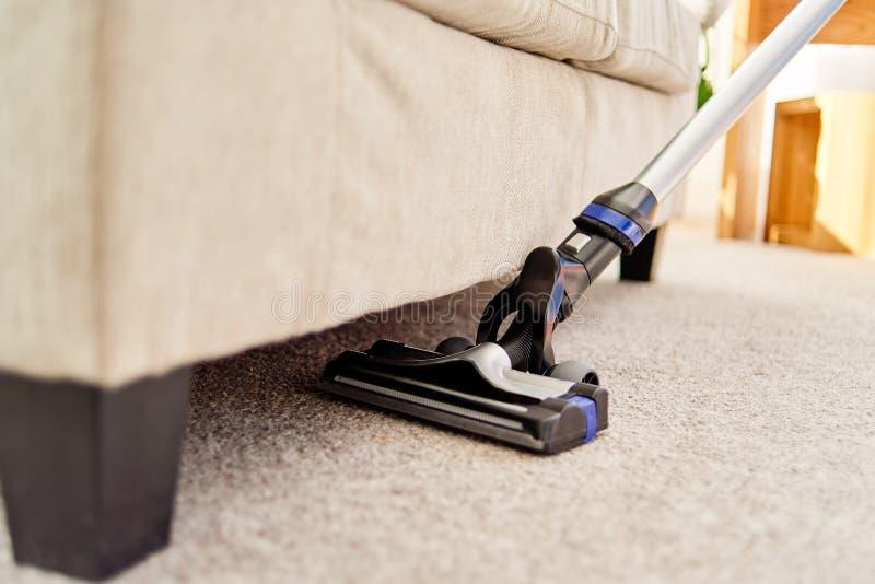 关闭在米黄地毯的现代吸尘器在地板上在客厅,拷贝空间 家事,家庭,春天cleanig 免版税库存图片