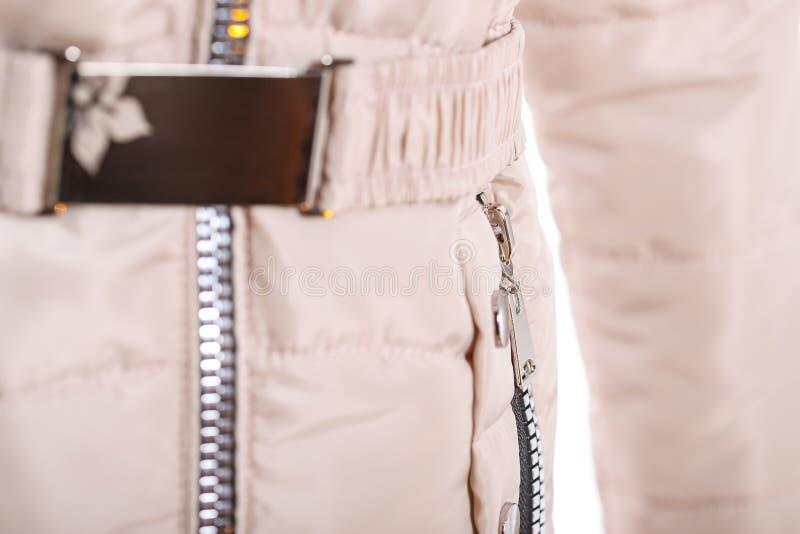 关闭在米黄夹克,冬天时尚成套装备的拉链 背景查出的夹克白色 库存照片