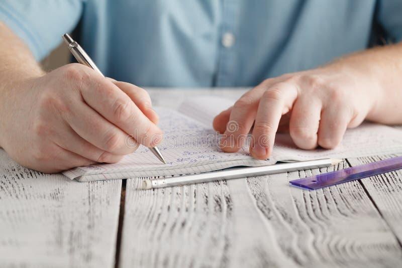 关闭在纸的男性` s手文字,文字杂乱算术, stude 图库摄影