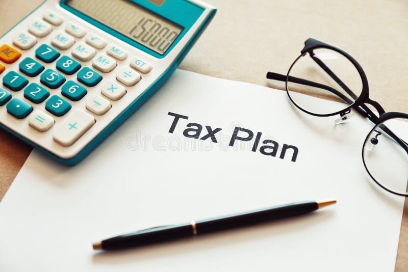 关闭在纸的税务计划词与计算器、笔和眼睛木桌的玻璃地方 库存图片