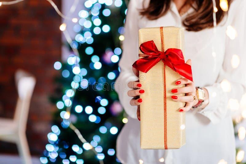 关闭在给圣诞礼物的妇女手上 库存图片