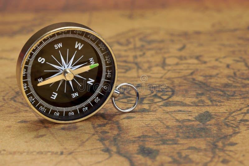 关闭在老地图的磁性指南针 免版税库存照片
