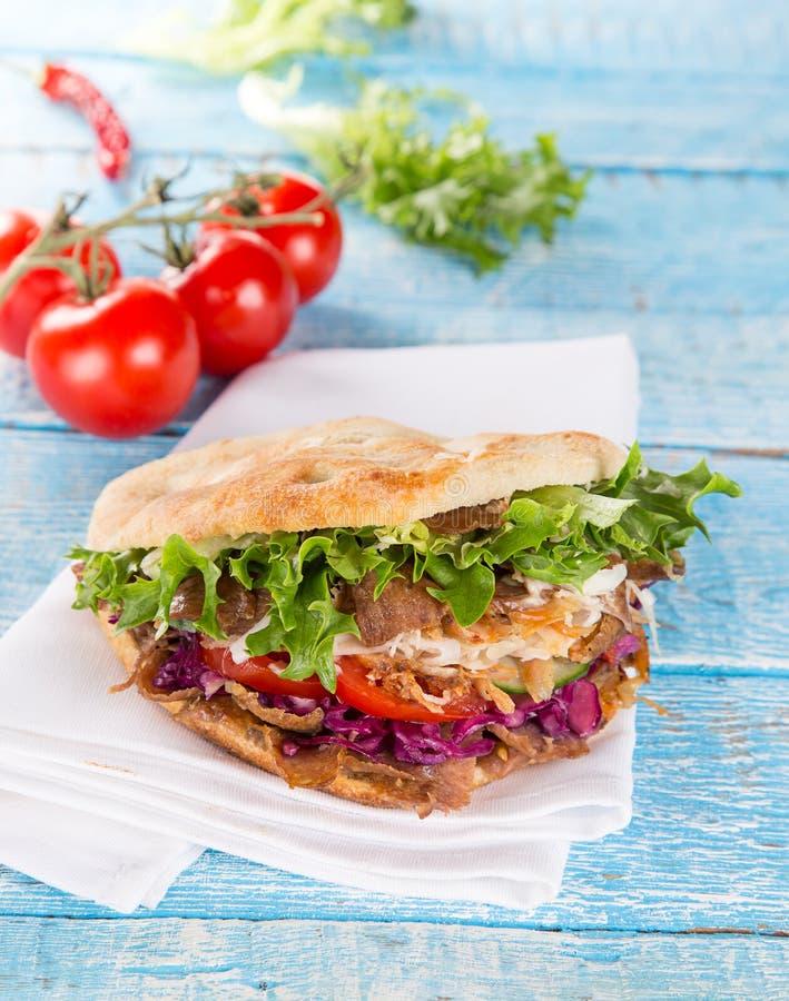 关闭在老木桌上的kebab三明治 库存照片