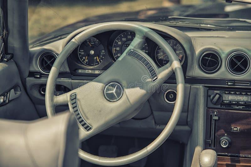 关闭在老葡萄酒默西迪丝方向盘和驾驶舱 免版税库存图片