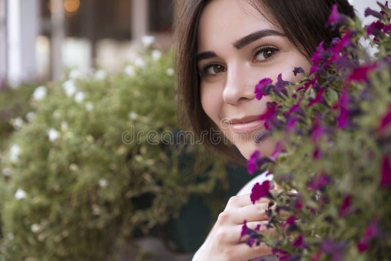 关闭在花的深色的妇女面孔 她快乐地微笑 r 图库摄影