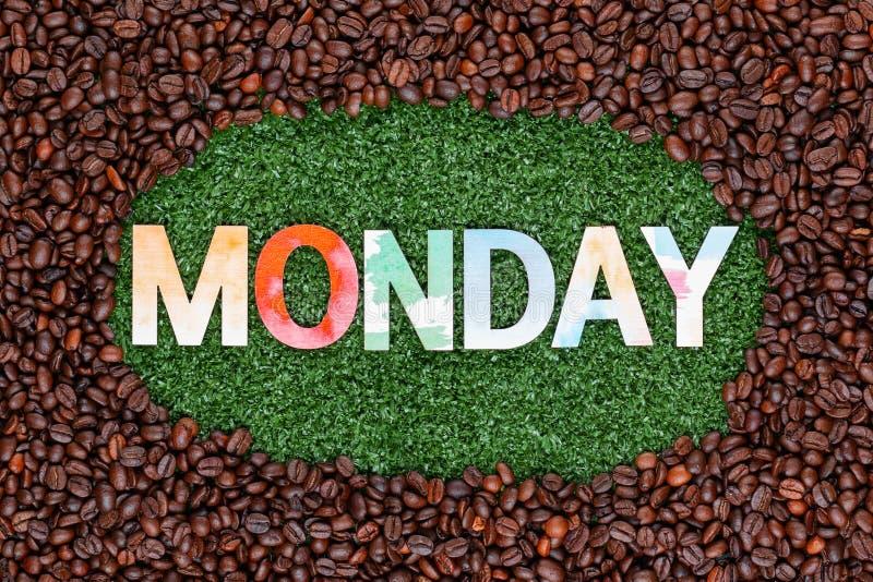 关闭在草的词星期一与咖啡豆 免版税图库摄影