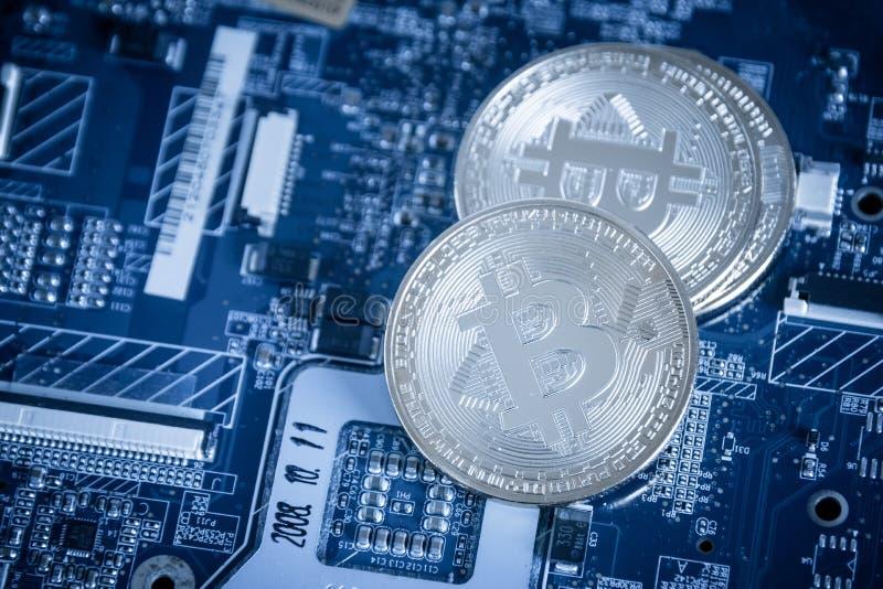关闭在蓝色计算机Mot上的银色数字式Cryptocurrency硬币 库存照片