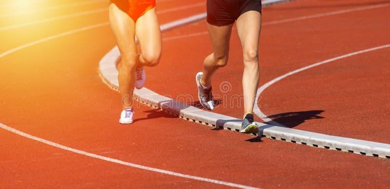 关闭在轨道领域的赛跑者脚 免版税库存图片