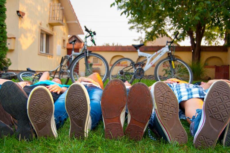 关闭在运动鞋的少年英尺,当位于在草时 免版税库存图片